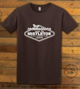 What Happens Under The Mistletoe Stays Under The Mistletoe Graphic T-Shirt - brown shirt design